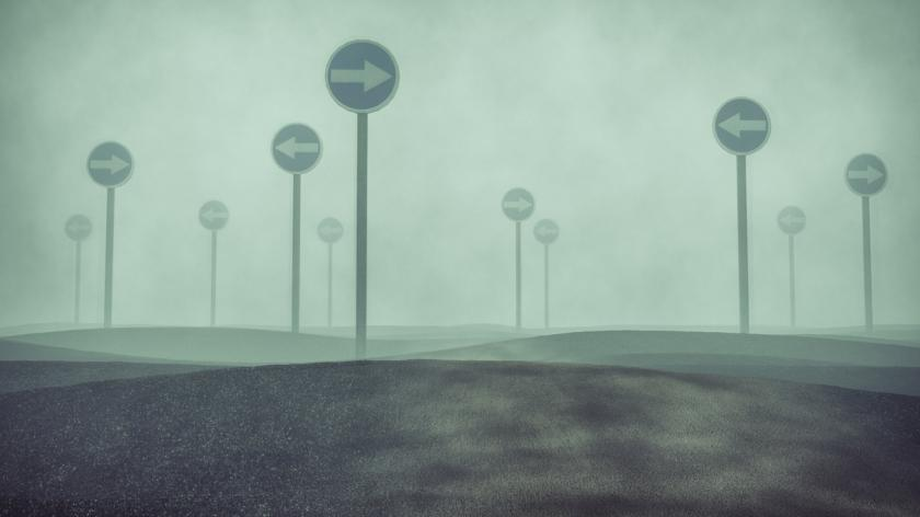 Confused foggy landscape with traffic signs