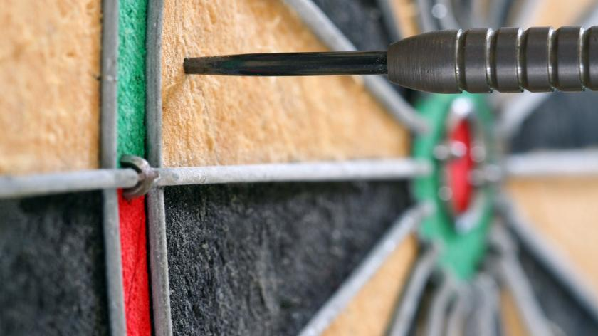 Side view close-up of single dart in a dartboard