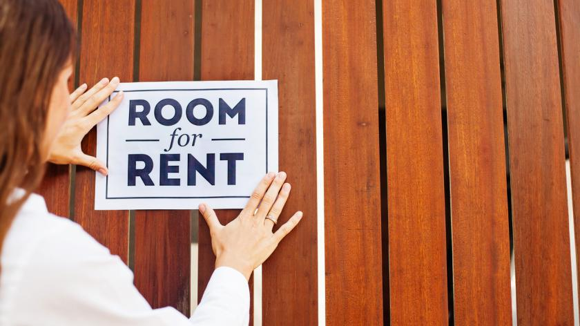 House owner attaching 'Room for rent' sign on a wall
