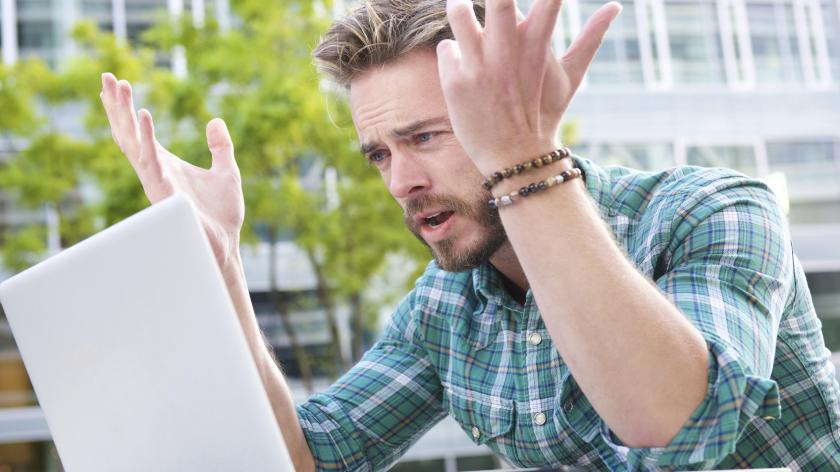 man reacting in a confused manner at something on his laptop