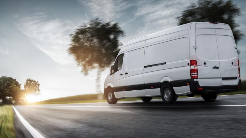 Delivery van drives on a road