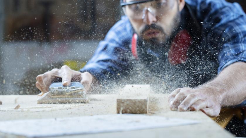 carpenter blowing wood shavings