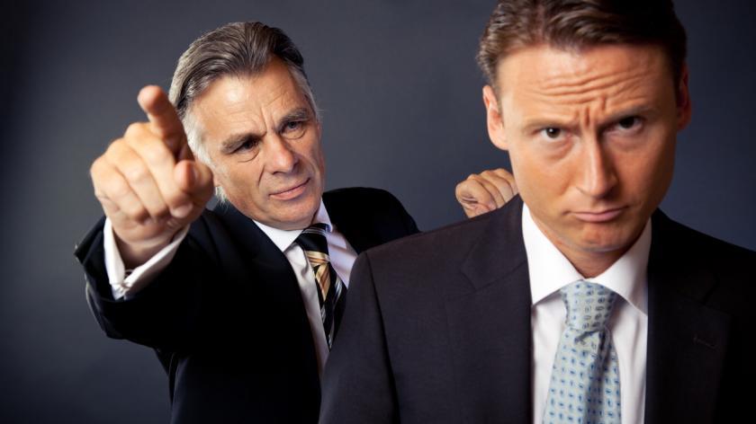 Senior businessman firing a younger employee