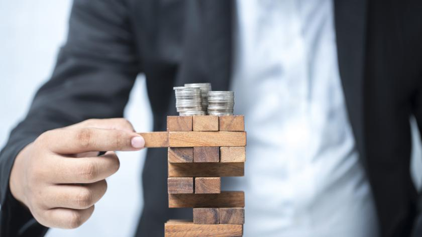 businessman stacking coins on a jenga tower - naturally