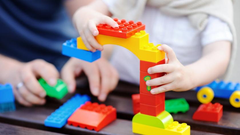 Father with his toddler son playing with colourful plastic blocks