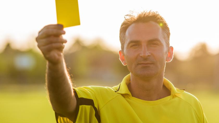 Referee showing yellow card at sunset