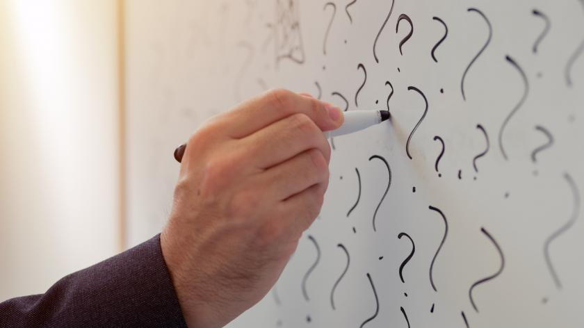 businessman writing question marks