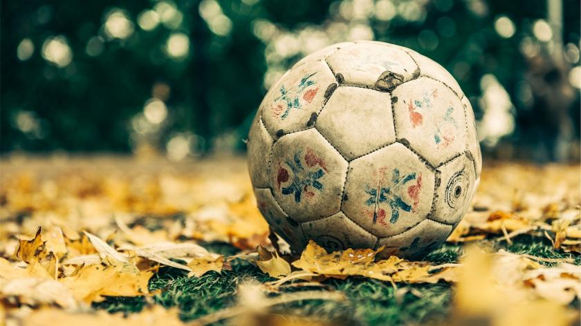 old football on a pile of leaves